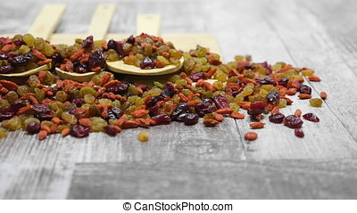 Mix of sweet dried fruits in wooden spoon on wooden...