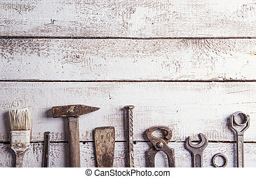 Desk of a carpenter with various tools. Studio shot on a wooden background.