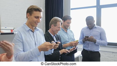 Mix Race Group Of Business People Texting Online Use Using Cell Smart Phones And Tablet Computers Messaging In Modern Office