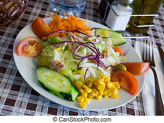 Mix salad with vegetables, boiled carrot, corn and lettuce at plate