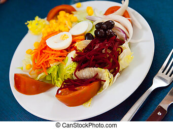 Mix salad with vegetables, prune, boiled beet and lettuce