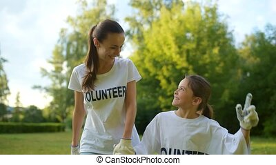 Mixed aged volunteers holding hands together and smiling