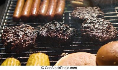 Mixed american barbecue food on hot grill. Hamburgers, hotdogs, corn being grilled. Tasty composition. Outdoor party.