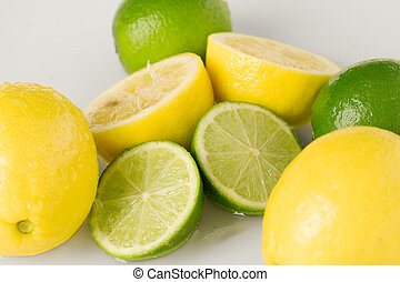 Mixed citrus - Refreshing lemons and limes on white...