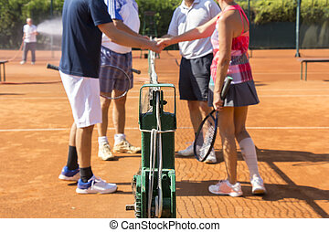 Mixed doubles tennis players shake hands before and after the tennis match