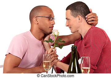 Attractive young mixed ethnicity gay, homosexual couple, Caucasian and African American in kitchen, celebrating valentine with champagne and flower. Studio, white background.