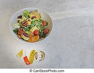 Mixed green and purple salad with measuring tape