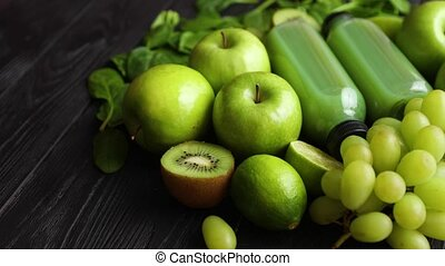 Mixed green fruits and vegetables placed on black wooden table
