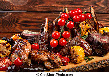 Mixed Grilled meat and vegetables on wooden background
