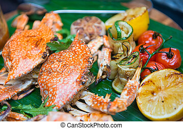Mixed grilled seafood with side dishes on banana leaf