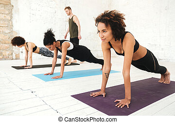 Mixed group of young people doing yoga class