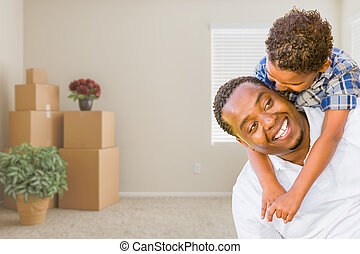 Mixed Race African American Father and Son In Room with Packed Moving Boxes