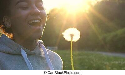 Mixed Race African American girl blowing dandelion at sunset...