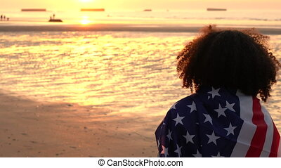 Mixed race African American girl teenager female young woman wrapped in an American US Stars and Stripes flag on a beach at sunset or sunrise
