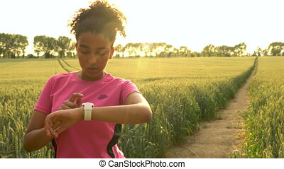Mixed race African American girl teenager female young woman runner using smart watch and running on path through field of barley or wheat crops at sunset