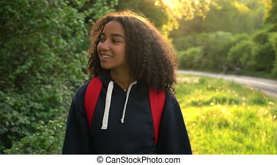 Mixed race African American girl teenager female young woman hiking at sunset