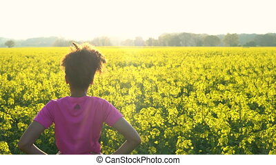 Mixed race African American girl teenager female young woman resting after running or jogging in field of yellow flowers