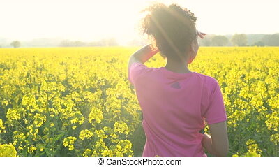 Mixed race African American girl teenager female young woman resting drinking bottle of water after running or jogging in field of yellow flowers