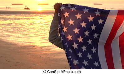Mixed race African American girl teenager female young woman holding an American US Stars and Stripes flag on a beach at sunset or sunrise