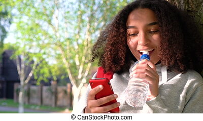 mixed race African American girl teenager leaning against a tree with a red backpack drinking from a water bottle and using a cell phone app