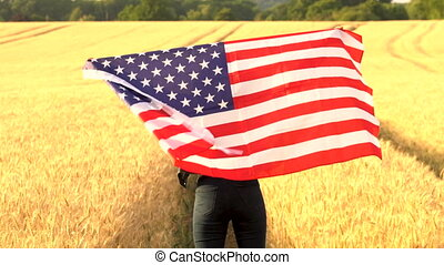 Mixed race African American girl teenager female young woman wrapped in an American US Stars and Stripes flag in a wheat field at sunset or sunrise