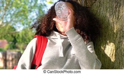 mixed race African American girl teenager leaning against a tree drinking water using cell phone