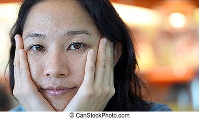 Mixed race Asian woman looking at camera with natural skin tone with no make up, real beauty