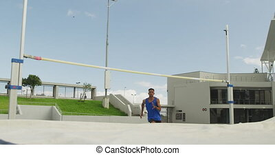 Mixed race athlete doing high jump - Front view of a mixed ...