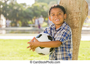 Mixed Race Boy Holding Soccer Ball in the Park