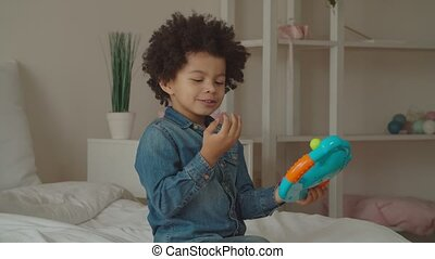 Mixed race boy playing with toy steering wheel