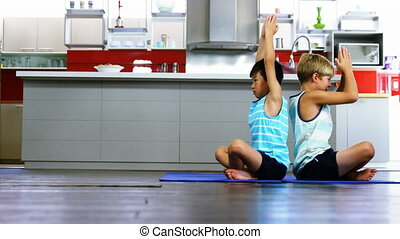 The words Flatten the Curve written over two boys practising yoga. Public health pandemic coronavirus Covid 19 social distancing and self isolation in quarantine lockdown concept digital composite
