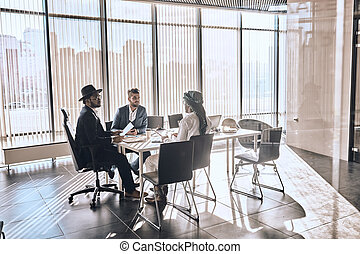 mixed race business people chatting in modern office