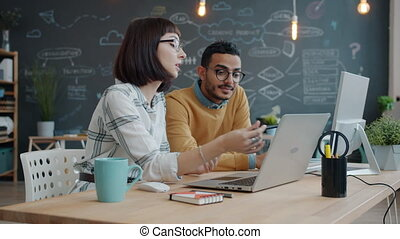 Mixed race business team man and woman talking in office looking at laptop screen