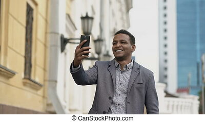 Mixed race businessman having online video chat in business conference using smartphone
