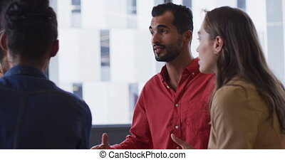 Mixed race businessman in a meeting with diverse group of colleagues