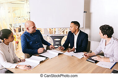 Mixed race businessman leading his team in their business meeting