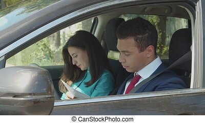 Mixed race businesspeople in car analyze documents -...