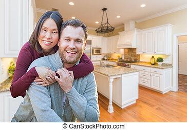 Mixed Race Caucasian and Chinese Couple Inside Beautiful Custom Kitchen.