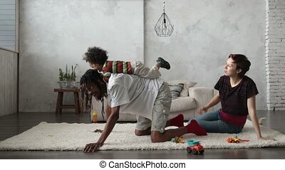 Mixed race child riding on father's back at home