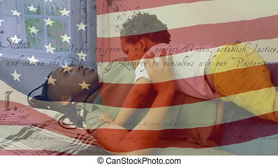 Animation of U.S. flag waving with U.S. Constitution text rolling over African American woman playing with her daughter. United States of America flag and holiday concept digital composition