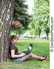 Mixed race college student sitting on the grass working