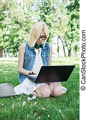 Mixed race college student sitting on the grass working on laptop