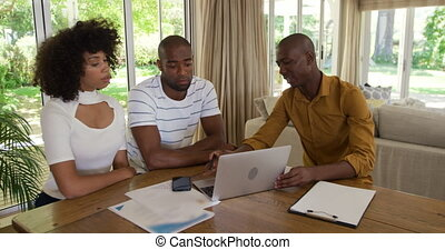Side view of a mixed race couple sitting by a table in an apartment with a mixed race man sitting by them, using laptop, talking and discussing, in slow motion