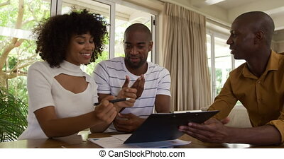 Side view of a mixed race couple sitting by a table in an apartment with a mixed race man sitting by them, a woman is signing a contract, smiling, in slow motion