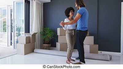 Mixed race couple dancing together in between cardboard boxes at new apartment house