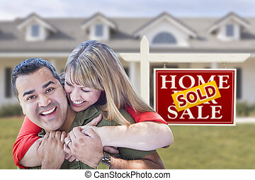 Mixed Race Couple in Front of Sold Real Estate Sign and House