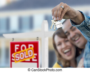 Mixed Race Couple in Front of Sold Real Estate Sign and House with Keys