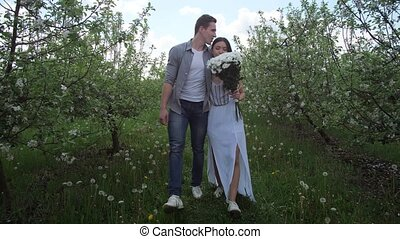 Mixed race couple laughing walking in orchard