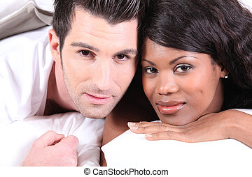 Mixed race couple laying in bed