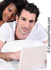 Mixed race couple lying on a bed